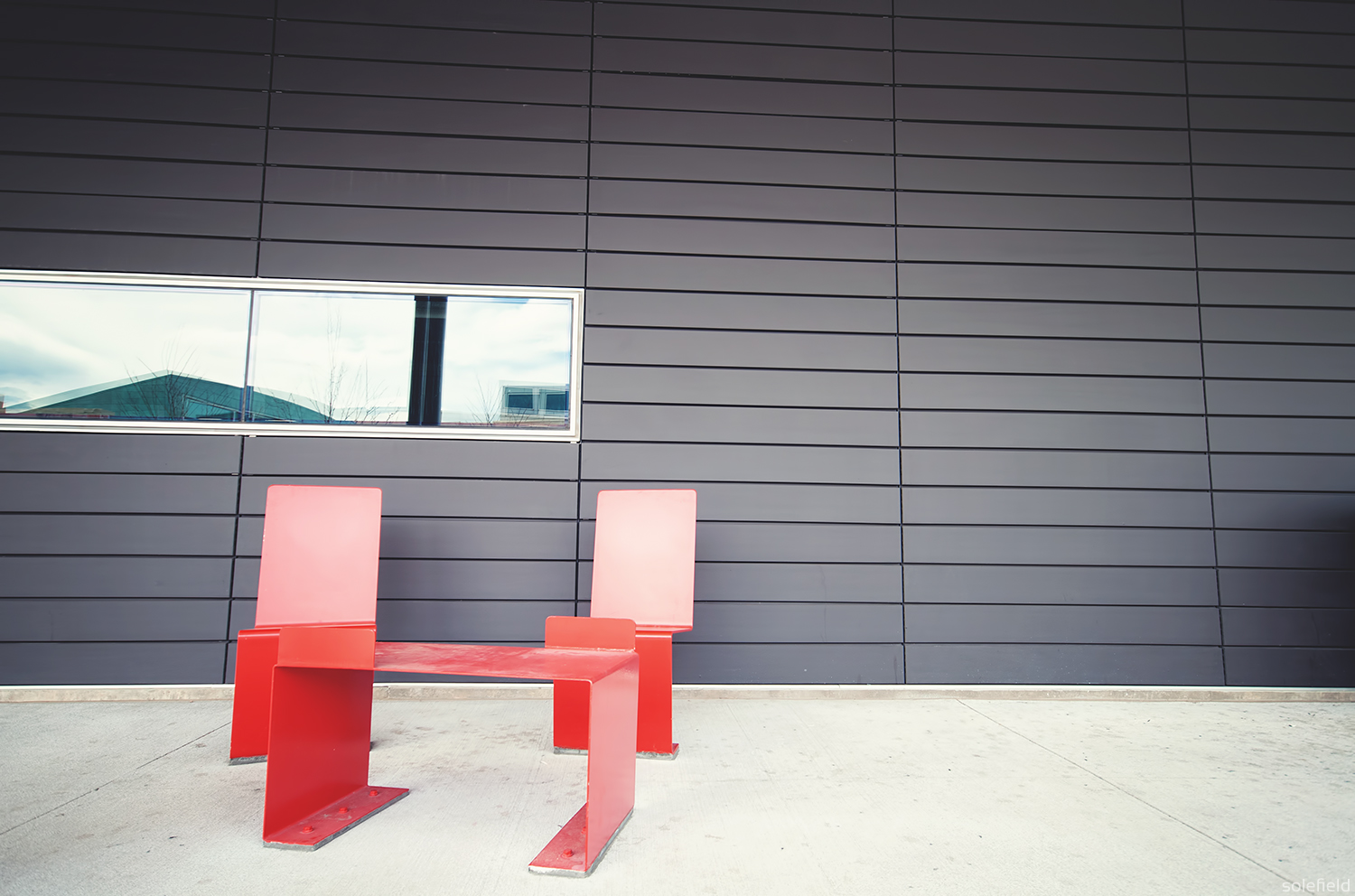 Red chairs in front of grey wall