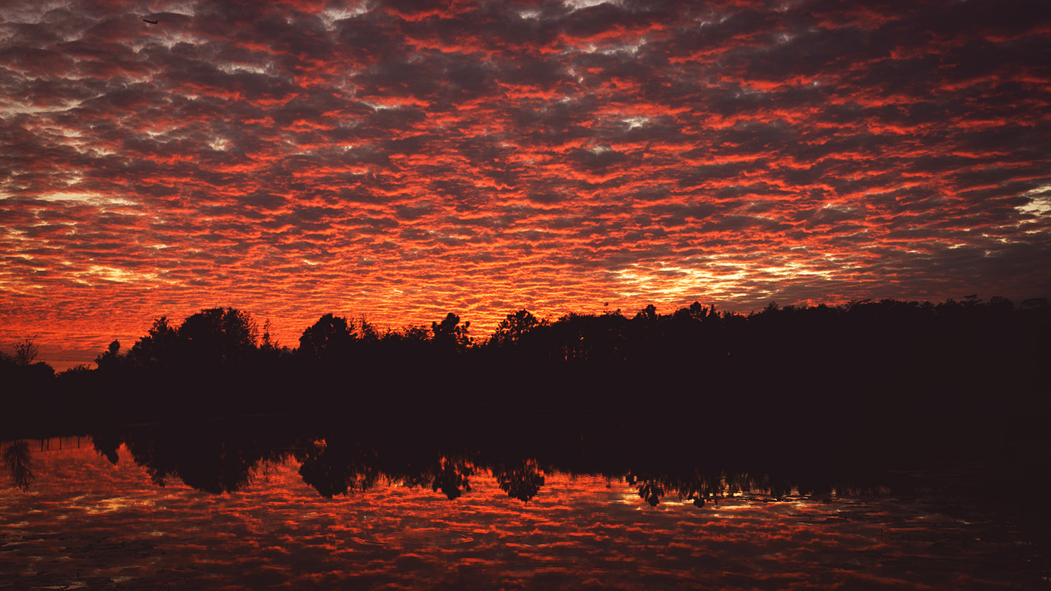 Sunset with dramatic clouds reflecting in lake