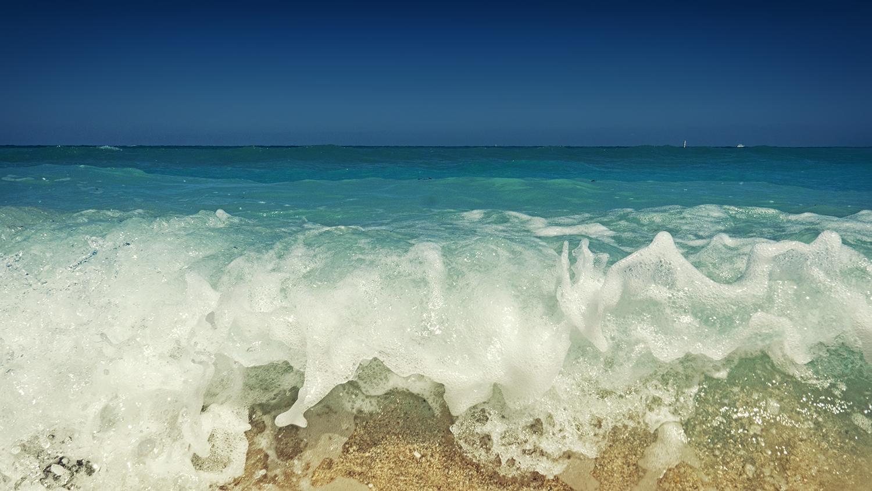 close view of waves crashing on beach