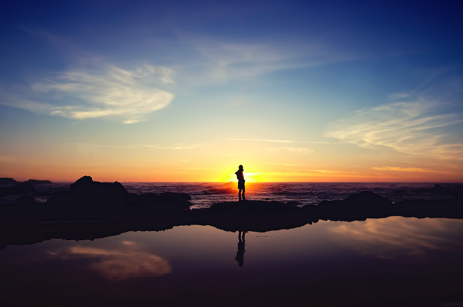 Silhouette of woman watching sunset over ocean